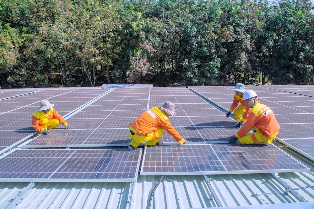 Local workers set up sustainable solar panels.